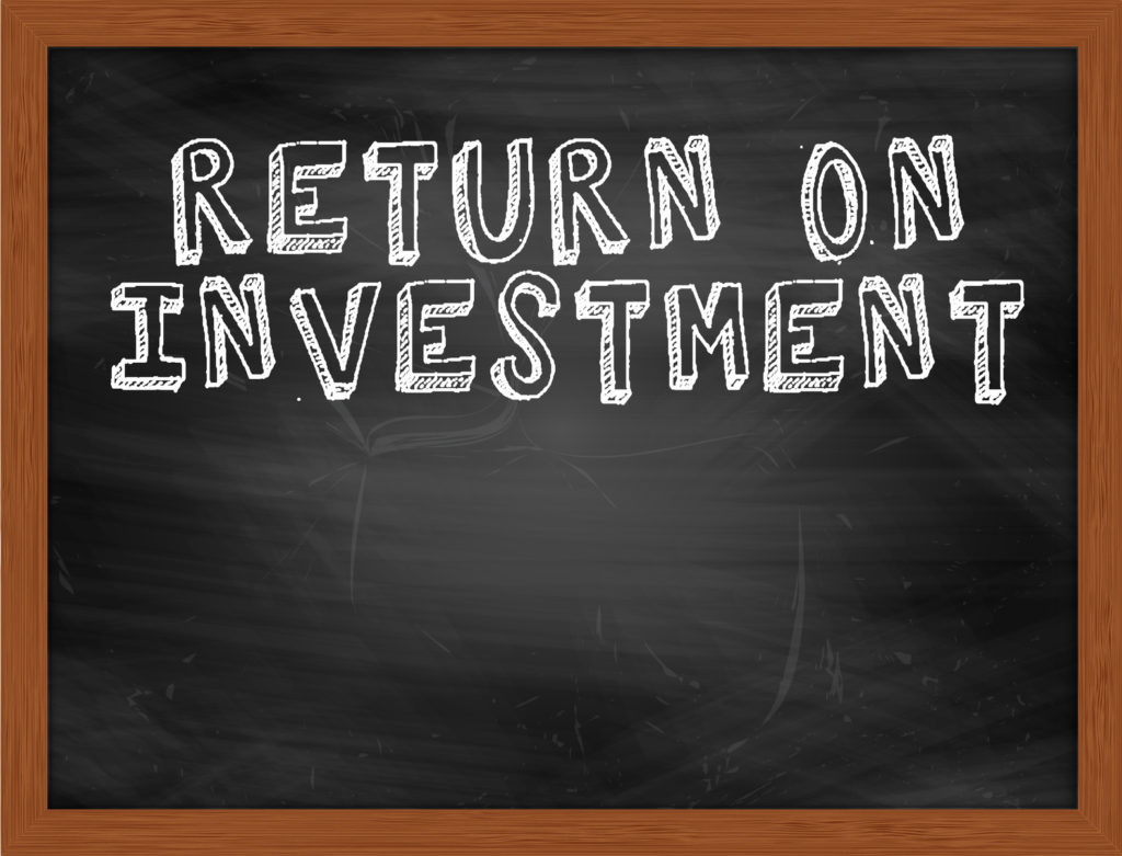 RETURN ON INVESTMENT handwritten chalk text on black chalkboard